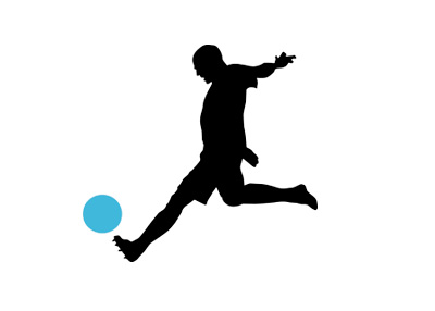 Silhouette of a football player about to kick the ball