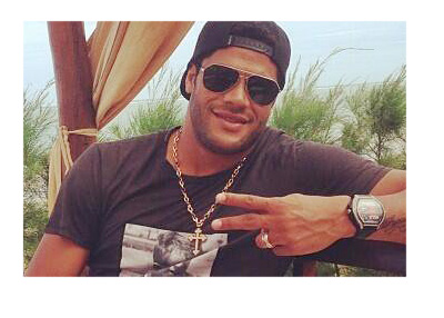 Hulk is relaxing with palm trees in the background.  Large gold chain around his neck and sunnies