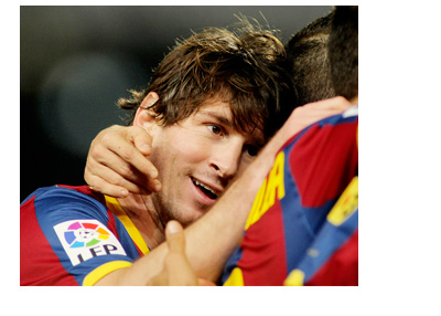 Long haired Lionel Messi celebrating a goal with Barcelona FC players