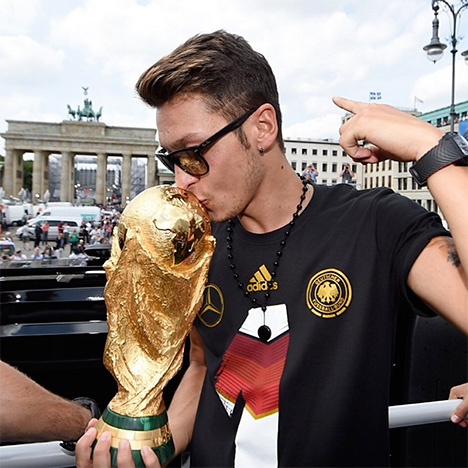 Mesut Ozil is kissing the World Cup trophy