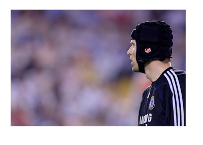 Petr Cech, wearing a Chelsea FC jersey, is looking into the distance.  Linked with a move to Arsenal