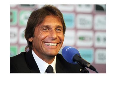 Antonio Conte with a big smile on his face.  At a press conference.
