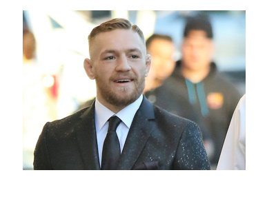 Conor McGregor strolling down the street in a fancy suit.  Big smile on his face.