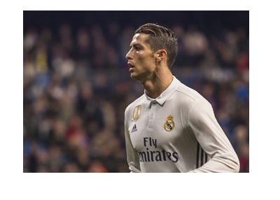 Cristiano Ronaldo in action for Real Madrid - The year is 2017 - White home kit with a winning badge imprinted in golden yellow.