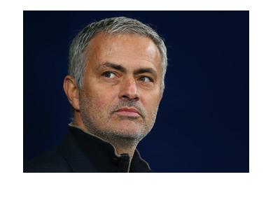 Jose Mourinho is looking into the distance.  Smirking perhaps.
