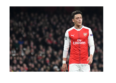 Mesut Ozil wearing the Arsenal home kit.  A little confused on the pitch.  Walking.