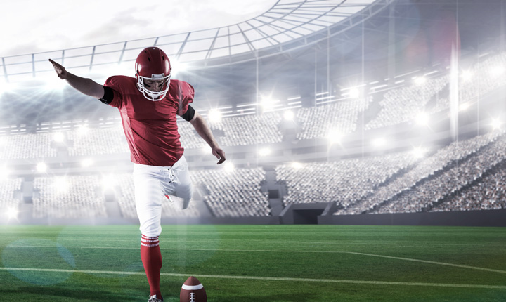 The NFL player is kicking the ball during the goal kick in the game in front of a full stadium.  Featured article is focused on football betting tips.