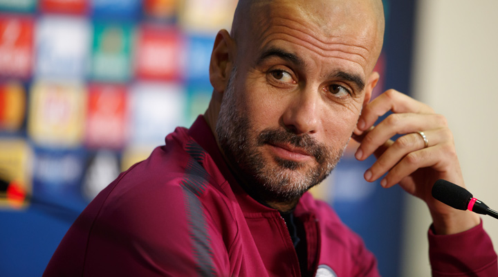 Manchester City manager, Pep Guardiola, with a half smile during a press conference after a Champions League match.  The season is 2017/18 and his team are the favourites to win the tournament coming into the round of 16.