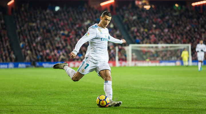 Real Madrid forward, Cristiano Ronaldo, is photographed shooting the ball.  The year is 2017.  He is wearing the home white jersey.