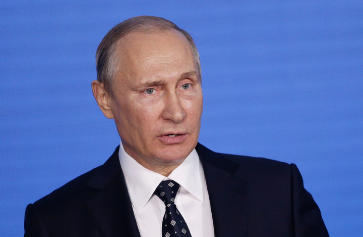 Russian president, Vladimir Putin, photographed during a speach.  Blue background is behind him.