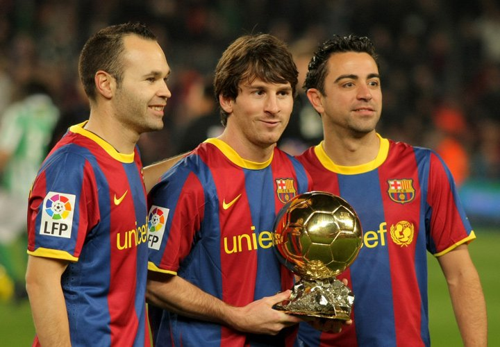 Ballon Dor in the hands of Messi, who is standing next to Xavi and Iniesta.  The good old Barcelona FC days.