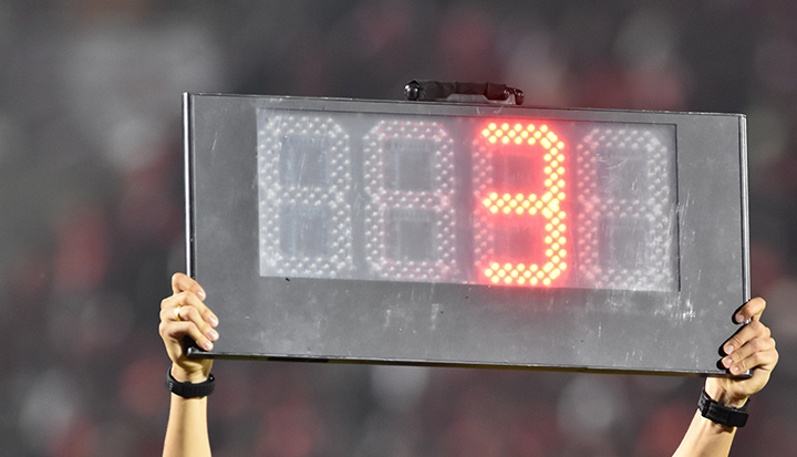 The referee is holding up a sign showing the minutes of extra time to be added at the end of the soccer match.  This time is also called injury / stoppage time.